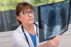 Female doctor examining x-ray report. In medical office stock photo