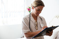 Female doctor examining reports in retirement home. Smiling female doctor examining reports in retirement home Royalty Free Stock Images