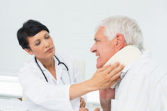 Female doctor examining a senior patients neck Royalty Free Stock Images
