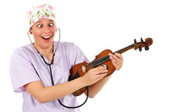 Female doctor examining a violin with stethoscope royalty free stock images