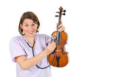 Female doctor examining a violin with stethoscope Royalty Free Stock Photo