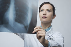 Female doctor examining x-ray image Stock Photos