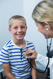 Female doctor examining young patient with a stethoscope Royalty Free Stock Photography