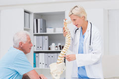 Female doctor explaining anatomical spine to senior man Stock Photo