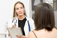 Female doctor explaining diagnosis to her young woman patient. Stock Image