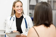 Female doctor explaining diagnosis to her young woman patient. Stock Photos