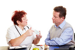 Female doctor explaining medication. Female doctor explaining side effects of medication to a patient Royalty Free Stock Photos