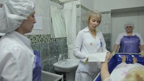 A female doctor explains to nurses how to wash a sedentary patient using innovative technologies. A female doctor in a white coat explains to nurses how to stock footage