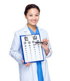 Female doctor with eye chart and glasses Stock Photo