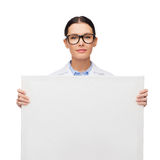 Female doctor in eyeglasses with white blank board. Healthcare, advertisement and medicine concept - smiling female doctor in eyeglasses with white blank board Royalty Free Stock Photos
