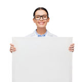 Female doctor in eyeglasses with white blank board. Healthcare, advertisement and medicine concept - smiling female doctor in eyeglasses with white blank board Stock Image
