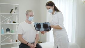 Female doctor in face mask showing complications from Covid-19 on lungs x-ray to male patient. Portrait of physician