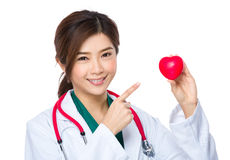 Female doctor finger point to heart ball. Isolated on white background stock photo
