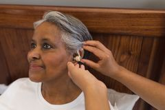 Female doctor fitting senior woman with hearing aid. Close-up of African American female doctor fitting senior African American woman with hearing aid at home royalty free stock photos