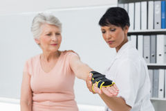 Female doctor fixing wrist brace on senior patients hand Stock Photo