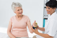 Female doctor fixing wrist brace on senior patients hand Royalty Free Stock Photography