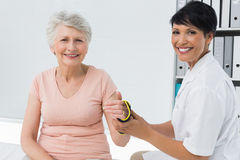 Female doctor fixing wrist brace on senior patients hand Stock Photos