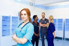Female doctor in front of team, looking at camera with medical team in background. Multiracial team of young doctors in. Asian male doctor in front of team Royalty Free Stock Image