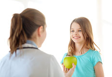 Female doctor giving apple to smiling little girl Stock Photos