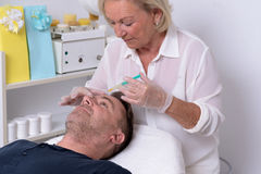 Female Doctor Giving Injection to Patient. Middle Aged Female Doctor Giving Injection to the Face of a Male Patient Inside her Clinic Royalty Free Stock Images