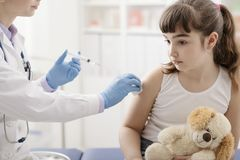 Female doctor giving an injection to a young cute girl stock images