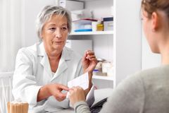 Female Doctor is giving a medical prescription to a patient, doctor´s order royalty free stock photography