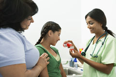 Female Doctor Giving Medicine To Girl. With mother in the clinic royalty free stock photo