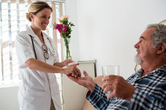 Female doctor giving medicines to senior patient. In nursing home Stock Photos