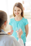 Female doctor giving pills and water to child Royalty Free Stock Photography