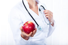 Female doctor giving red apple Royalty Free Stock Photography