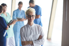 Female doctor with glasses and blonde hairstyle standing in fron Royalty Free Stock Images