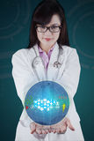 Female doctor with globe in her hands Stock Photography