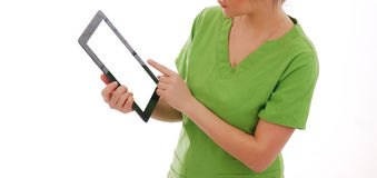 Female doctor in green medical suit holds tablet pc against white background. Female doctor in medical suit holds tablet pc against white background Royalty Free Stock Image