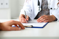 Female doctor hand hold silver pen filling patient history list Royalty Free Stock Photography