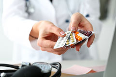 Female doctor hand holding pack of different tablet blisters stock images