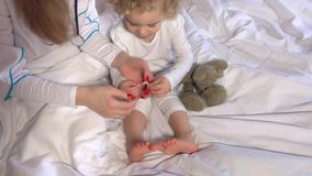 Female doctor hands stick strapping adhesive on cute little girl leg in bed. Handheld steadycam flycam movement shot. 4K UHD stock footage