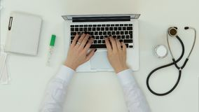 Female doctor hands typing on laptop royalty free stock images
