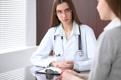 Female doctor having a talk with her patient  while sitting at the table near the window in hospital. Physician is read Royalty Free Stock Photo