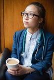 Female doctor having tea in clinic Stock Image