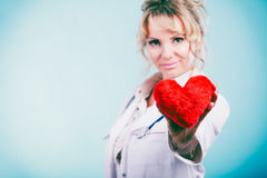 Female doctor with heart. Love from working and helping people. Mid age blonde doctor in white medical apron with heart on blue. Enjoy work concept royalty free stock photography