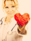 Female doctor with heart. Love from working and helping people. Mid age blonde doctor in white medical apron with heart. Enjoy work concept. Filtered stock photos