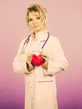 Female doctor with heart. Love from working and helping people. Mid age blonde doctor in white medical apron with heart. Enjoy work concept. Filtered royalty free stock images