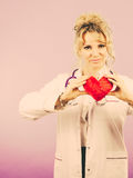Female doctor with heart. Love from working and helping people. Mid age blonde doctor in white medical apron with heart. Enjoy work concept. Filtered stock images