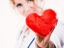 Female doctor with heart. Love from working and helping people. Mid age blonde doctor in white medical apron with heart. Enjoy work concept. Isolated on white royalty free stock photography