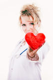 Female doctor with heart. Love from working and helping people. Mid age blonde doctor in white medical apron with heart. Enjoy work concept. Isolated on white stock image