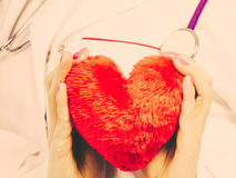 Female doctor with heart. Love from working and helping people. Part body female doctor in white medical apron with heart. Enjoy work concept. Filtered stock image
