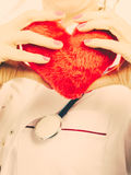 Female doctor with heart. Love from working and helping people. Part body female doctor in white medical apron with heart. Enjoy work concept. Filtered stock photo