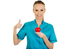 Female doctor with heart. Smiling female doctor with heart and thumbs up stock images