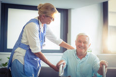 Female doctor helping senior man to walk with walker Royalty Free Stock Image