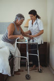 Female doctor helping senior woman to walk with walker. Female doctor helping senior women to walk with walker at home Stock Images